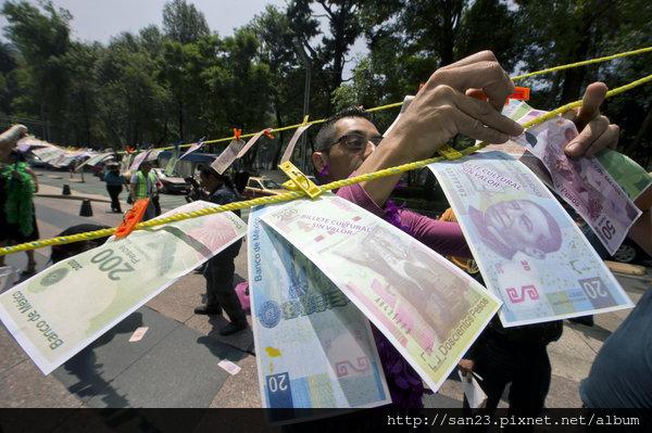 抗議中有人將假幣掛在滙豐銀行墨西哥城一家分行前。