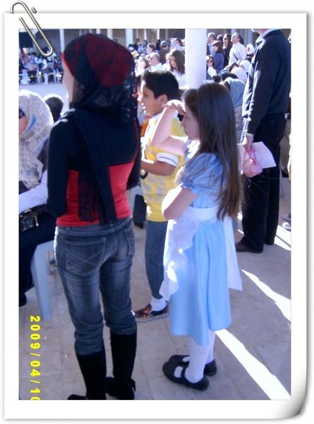 包頭巾的新潮阿拉伯女人與穿著戲服洋裝的阿拉伯小女孩