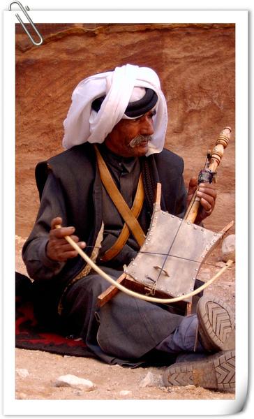 身穿貝都因傳統服飾的老人拉奏羊皮琴