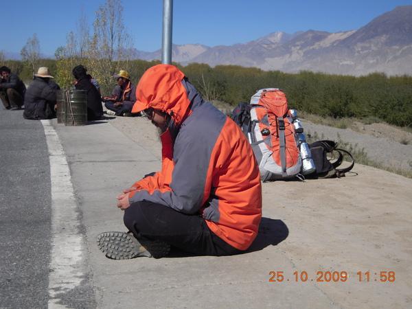 古魯坐在馬路旁等待車子,後面是我們的行李!.jpg