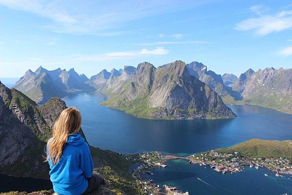 young-blonde-woman-sitting-on-rock-and-looking-at-mountains-and-lake.jpg