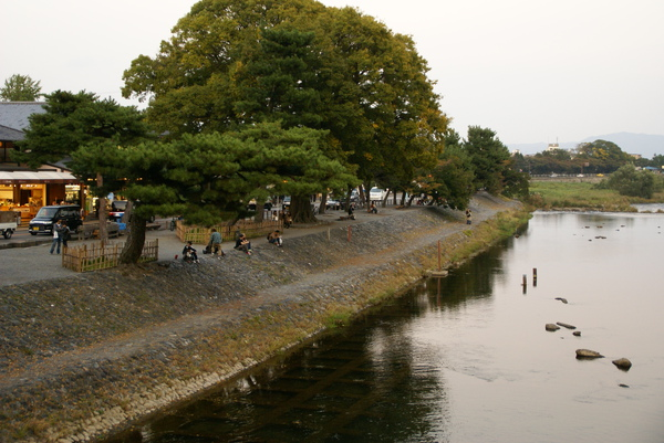 渡月橋往桂川河提望去 許多人席地而坐等著嵐山的日落
