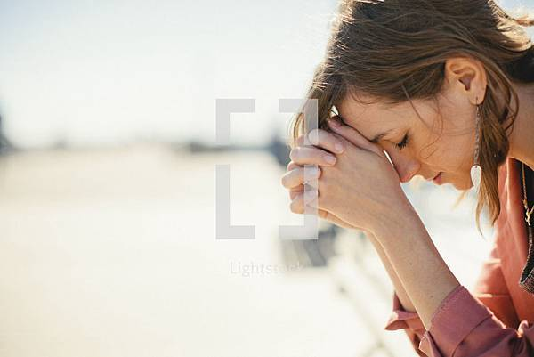 lightstock-4082-a-woman-bowing-her-head-in-prayer