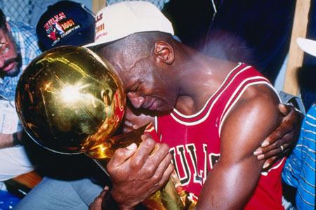 Series MVP and guard Michael Jordan of the Chicago Bulls hugs the championship trophy as the Bulls defeated the Los Angeles Lakers, 1991.jpg