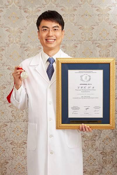 世樺牙醫診所院長溫世政醫師,圖為其發明的微創植牙器械得到日本天才發明獎金牌的照片