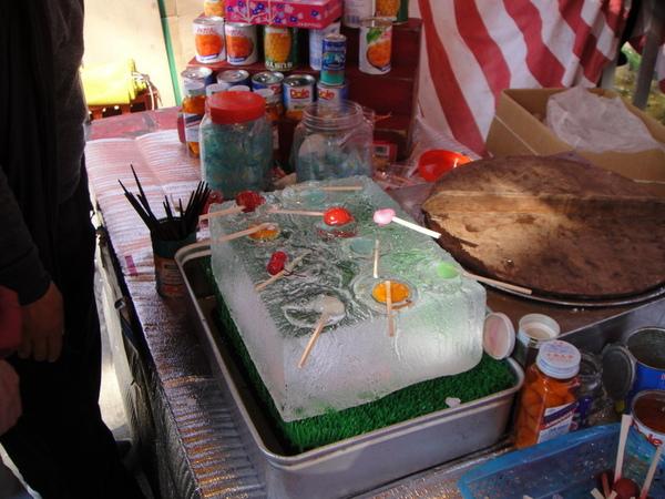 在冰塊上放著包著糖衣的醃漬梅子和水果