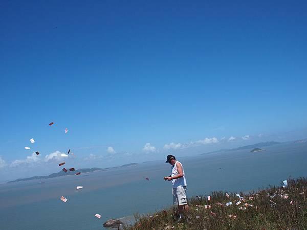 006一江山最高點的高地上,同行的友人向空中拋紙錢祭拜戰死的軍人.jpg