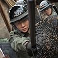 張家輝演出首持盾牌棍棒的鎮暴警察與村民對峙
