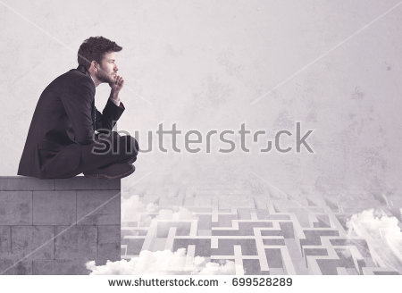 stock-photo-business-worker-sitting-on-concrete-building-edge-thinking-of-solving-a-maze-concept-with-699528289.jpg