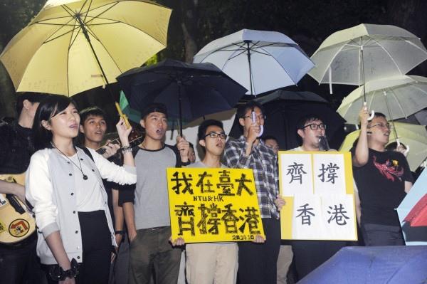 二十多名台灣大學港、澳僑生10日晚間冒雨在台大校門口集會,唱著歌曲「海闊天空」,聲援香港佔中行動。(記者廖振輝攝)