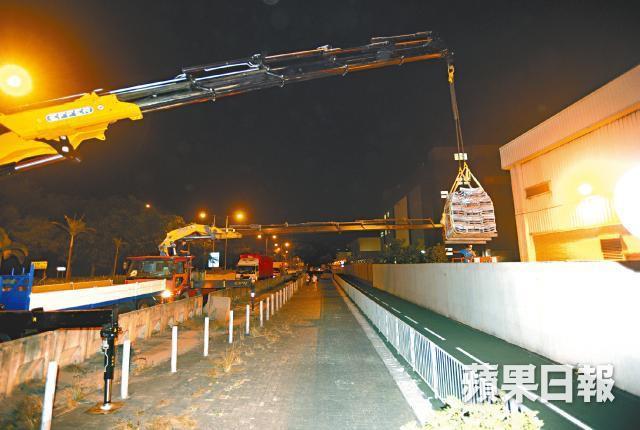 2014 ■昨凌晨,受包圍的《蘋果日報》,由吊臂車將報紙從廠房吊過圍牆運出市面。