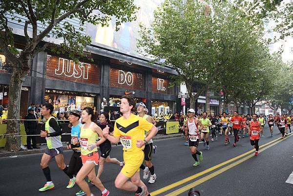 Nike上海淮海體驗店門口,民眾組成熱鬧的加油團隊為參賽者鼓勵打氣 (2)