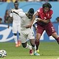 迦納球員Asamoah Gyan試著擺脫對手糾纏