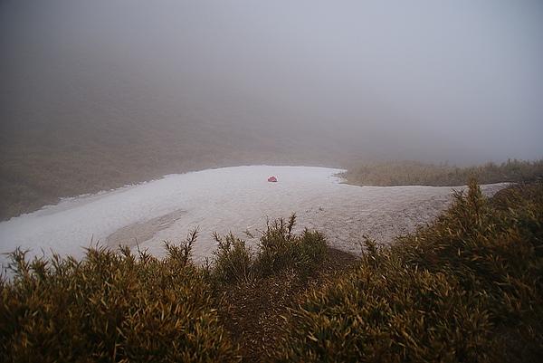 同事的帽子被風吹倒下方草坡的雪地,撿不回來了