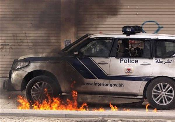 Riot police vehicle drives through a fire from a petrol bomb from anti-government demonstrators, during clashes Saturday