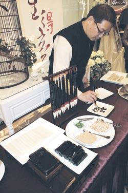 20110401工商時報:蘇杭餐廳副總經理黃延齡以甜點製成的毛筆,試範可吃、可寫的「文房四寶」甜點。
