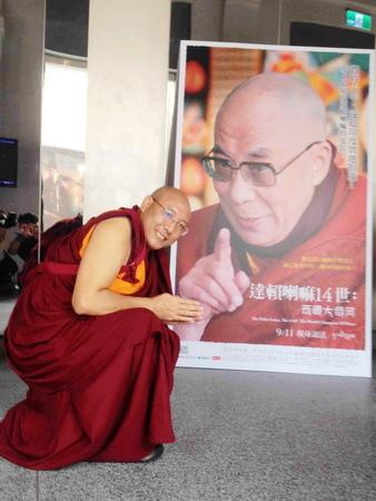 見悲青增在看到《達賴喇嘛14世》海報十分興奮,立刻蹲下擺出尊聽教誨的模樣拍照,十分頑皮可愛