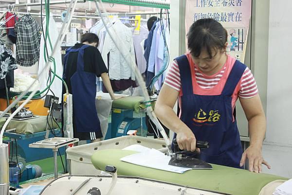 訓練有素的洗衣坊青年為衣物整燙