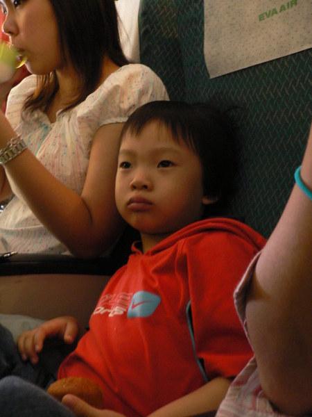 飛機上無聊的杜小昀,以及旁邊只顧著自己吃早餐、呆滯的小花阿姨