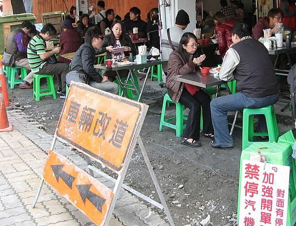因占用騎樓被市府連續開單的料理店,改占據施工中的路面擺設桌椅營業。(記者吳孟珉攝)