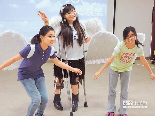 展翅天使劉麗紅(中)28日至善化國小演講,與學生互動,一同裝起翅膀,鼓勵孩子展翅高飛。(黃健誠攝)