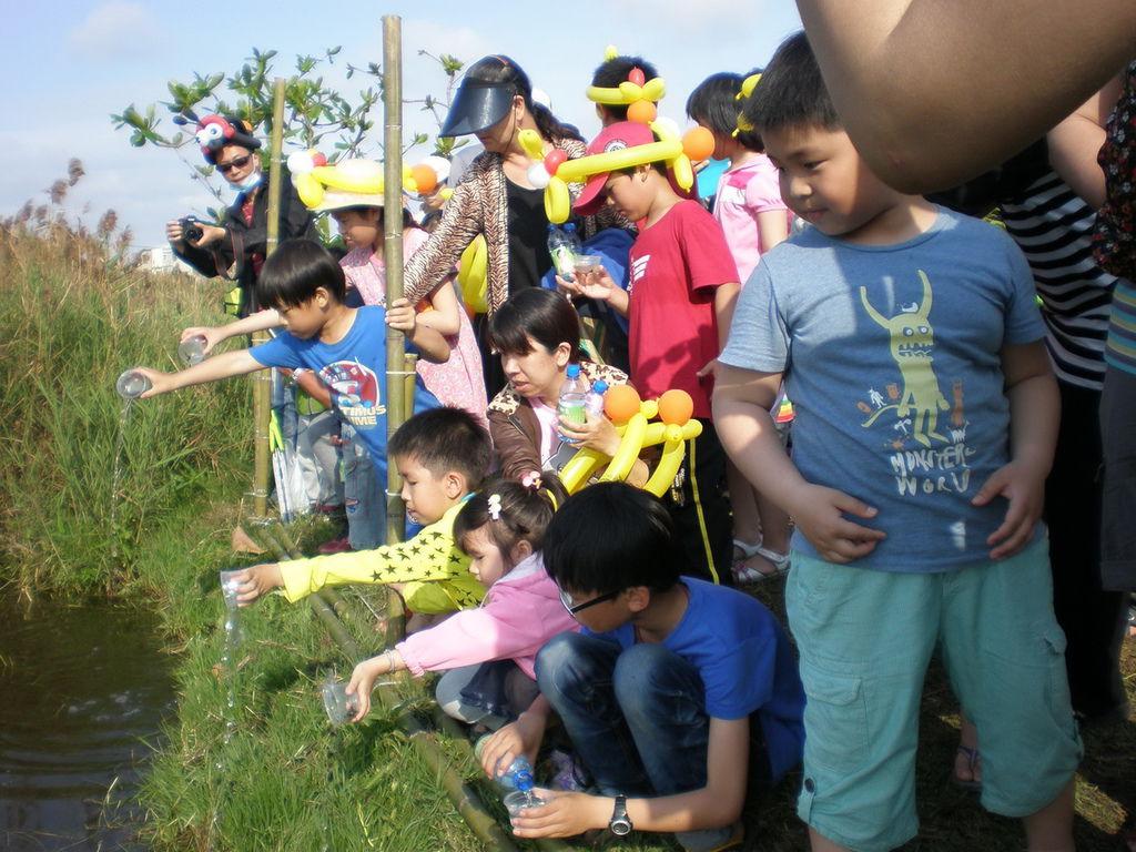 百餘名家長和省躬國小學生一起到灣裡人工濕地生態池,野放水生黃緣螢幼蟲,進行護育螢火蟲。(記者葉進耀攝)