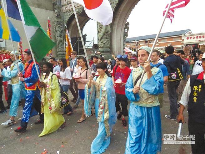 宗教鮮體驗  上百位來自不同國家的外籍生身穿古裝帶著壽桃向保生大帝祝壽,感受台灣的民俗文化。