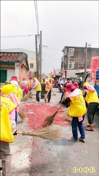 茅港里環保志工跟在遶境隊伍後面,迅速清掃滿地的鞭炮屑,恢復街道清潔。