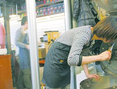 玻璃帷幕的烘焙室設有大型烘焙機,員工烘焙咖啡豆的模樣一目了然。