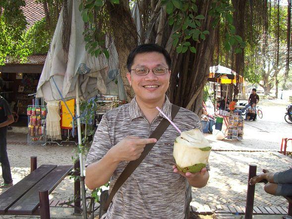 在 Wat Phra Mahathat 外面喝椰子水