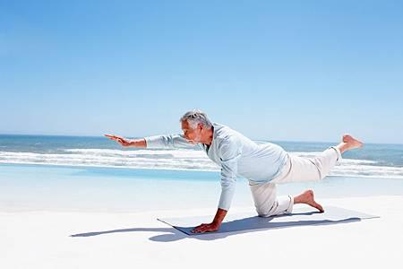 senior-man-doing-yoga-on-the-beach
