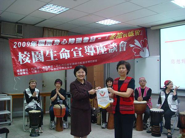 黃玉如老師(左)代表校方致贈一面旗幟感謝協會前來宣導.右為協