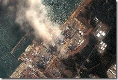 福島第一核電廠反應爐連續爆炸,圖為14日衛星照片顯示該廠不斷冒煙。(美聯社)