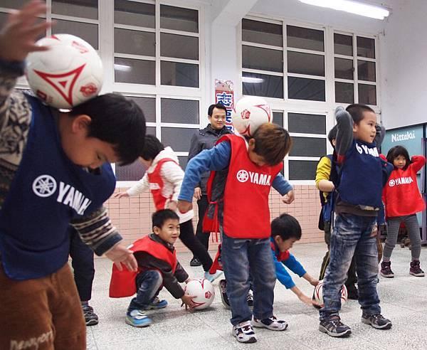 【YAMAHA CUP】教練指導停球、頂球,以分站趣味課程讓孩童體驗並學習足球正確觀念,圖中孩童練習後頸停球,訓練平衡能力