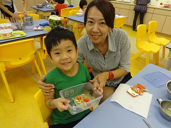 小朋友開心地和媽媽一起展示今天好吃的成品!