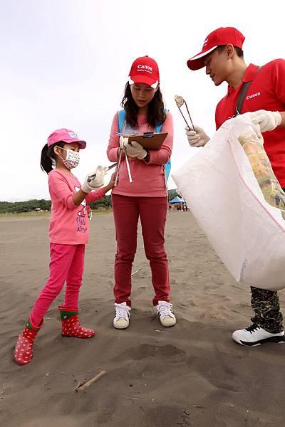 圖說三,Canon企業志工帶著小孩一起實際參與淨灘,除了付出一己之力、守護海岸之外,更透過親身參與作為機會教育,培養孩子環境保育的觀念。