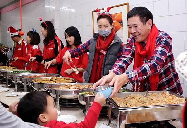 圖說四,鎌田篤 總裁與企業志工們及愛心大使張鈞甯造訪台北榮光育幼院,和院童在歡笑聲中共享聖誕晚餐,並貼心的幫院童夾菜