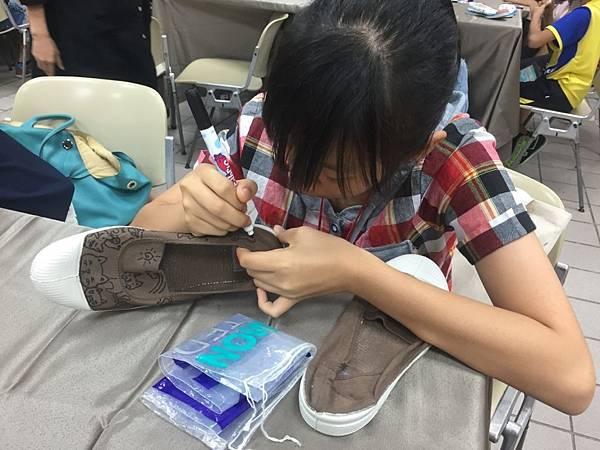 孩童在鞋子上彩繪出心愛的寵物