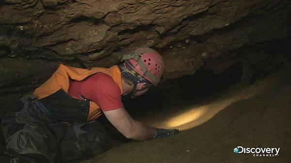 洞穴探勘者在狹窄地底隧道爬行