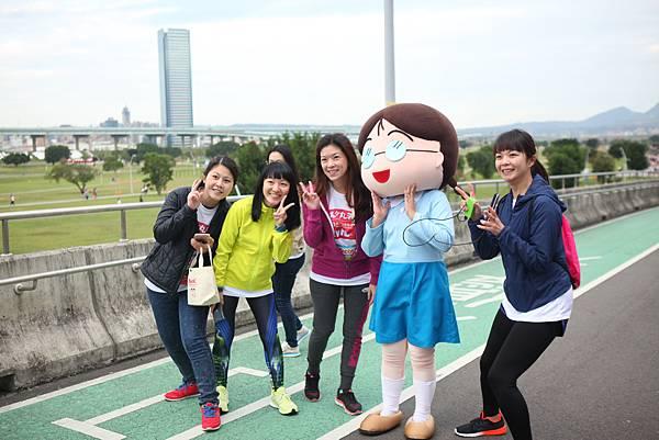 跑者們興奮地拿起手機和小玉人偶合照