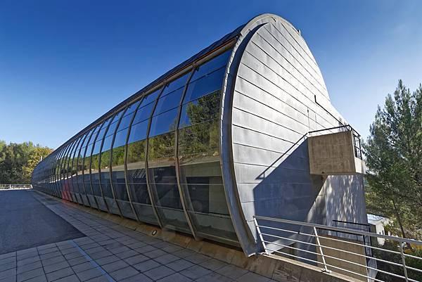 高50公尺寬20公尺的平躺圓柱狀設計中心被松樹林圍繞,水泥與玻璃窗形塑了輪廓分明的建築造型,室內使用釉面建材賦予地中海柔光氣息