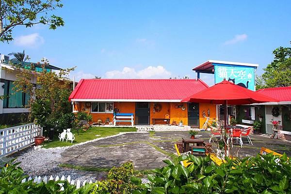 圖十:「貓天空寵物鄉村民宿」鮮豔大紅色磚瓦與綠草地互相輝映,牆面也都選用明亮的色彩,旅客們來到這邊,房客居住期間隨處可以見到悠閒走動的雞和懶惰的貓大爺