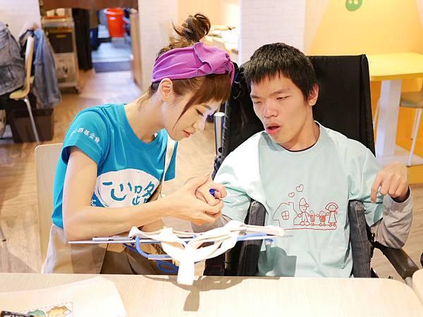 Lulu協助寬寬握住畫筆,完成自己的提袋創作.JPG