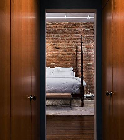 Brick-Wall-Studio-Apartment-by-Stephan-JAKLITSCH-GARDNER-narrow-hall-to-uncovered-four-poster-bed-on-area-rug-with-white-linen.jpeg