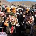 理塘-藏族婚禮-男方祈福(5)手持松類的枝葉沾桶子的水灑向新郎妹妹.jpg
