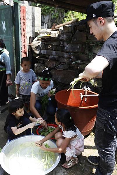 潘瑋柏和小朋友一起用木柴燒火準備午餐