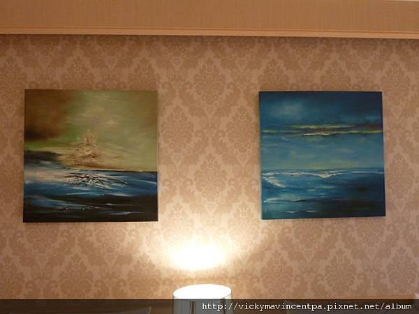 牆上掛著兩張鮮豔的油畫