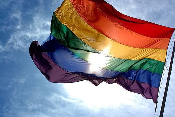 Rainbow_flag_and_blue_skies.jpg