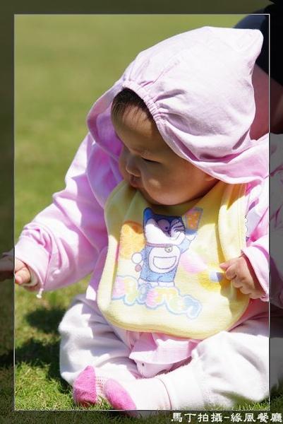 坐在草地上的小沛瑀,好奇的伸出手要踫草地.jpg