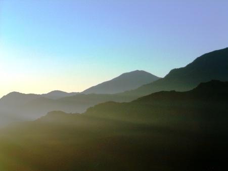 陽光微微照亮層層山巒
